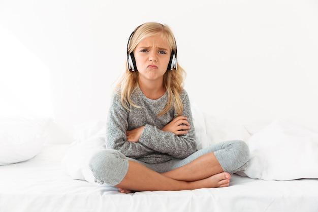 Chateado criança feminina em fones de ouvido, sentado com os braços cruzados e pernas na cama