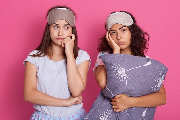 Chateado e cansado mulheres de pé contra o studio rosa