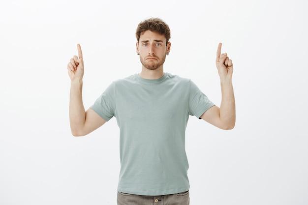 Chateado e miserável homem bonito em roupas da moda, levantando o dedo indicador e apontando para cima, entediado ou cansado após um longo dia de trabalho
