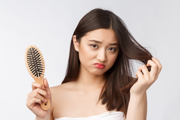 Chateado estressado jovem mulher asiática segurando cabelos secos danificados nas mãos sobre parede isolada branca
