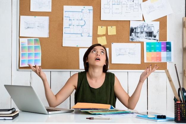 Chateado jovem empresária linda gesticulando, sentado no local de trabalho