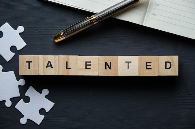 Chavão empresarial moderno - talentoso. vista superior no quebra-cabeça e bloco de notas com blocos de madeira. vista do topo.