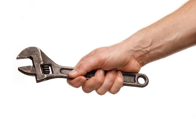 Chave ajustável nas mãos de um homem em um fundo branco isolado e close-up