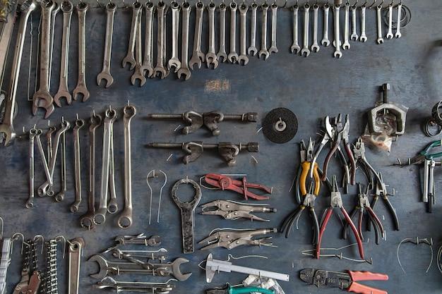 Chave, alicates, braçadeiras. muitas ferramentas mecânicas no fundo velho da placa de madeira.