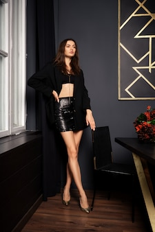 Chave baixa moça bonita em mini saia e jaqueta em pé perto da mesa