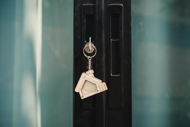Chave da casa em um chaveiro de prata em forma de casa na fechadura de uma porta de entrada