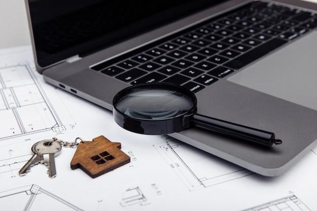 Chave da casa, laptop e uma lupa em um desenho. conceito de construção imobiliária