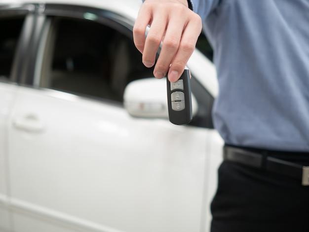 Chave da exploração do homem na concessionária de automóveis moderna. feche a mão do cardealer dando a chave do carro para o cliente