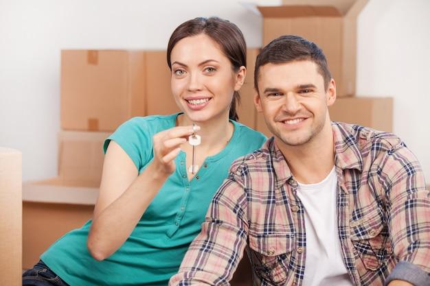 Chave da nova casa. lindo casal jovem sentado perto um do outro sorrindo enquanto segura a chave da casa