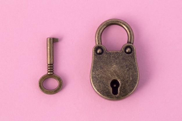 Chave de bronze e cadeado em papel rosa claro, imagem de fundo