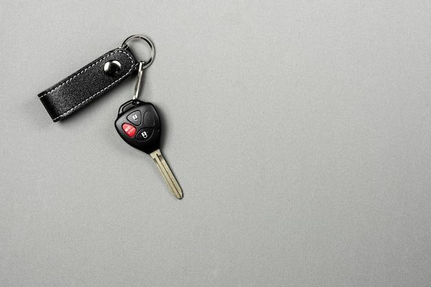 Chave de carro com controle remoto em fundo cinza.