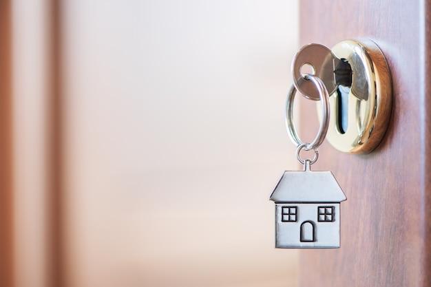 Chave de casa com chaveiro de casa no buraco da fechadura da porta. compre um novo conceito de casa