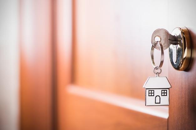 Chave de casa em um chaveiro de prata em forma de casa na fechadura de uma porta de entrada marrom
