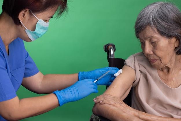 Chave de croma, enfermeira fazendo injeção de vacina para mulher sênior.