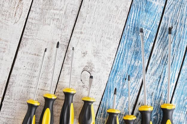 Chave de fenda definida em um fundo de madeira, vista superior, copie o espaço, muitas chaves de fenda no fundo azul e cinza de pranchas antigas