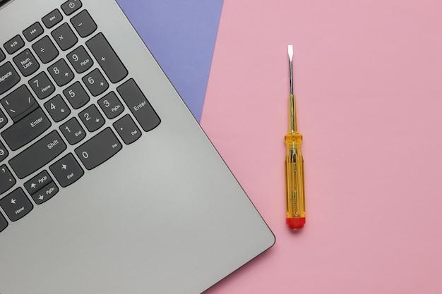 Chave de fenda do laptop do reparo do laptop do centro de serviços em fundo rosa roxo