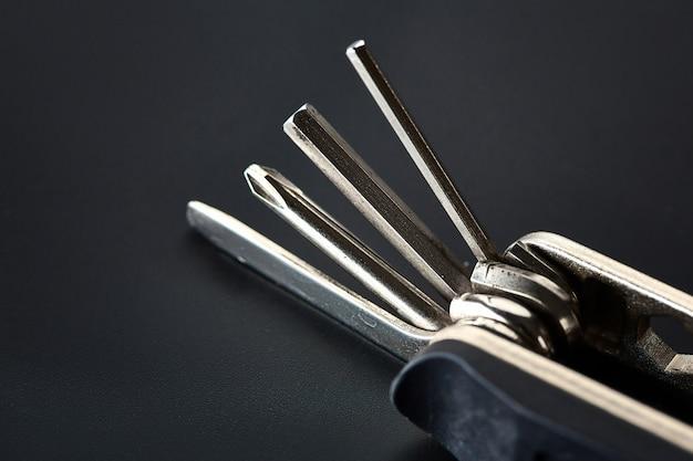 Chave de fenda dobrável com diferentes bits, closeup. instrumento profissional, equipamento de trabalho, ferramentas de aparafusamento