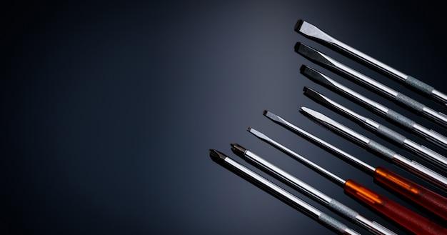 Chave de fenda e furador central. ferramentas manuais mecânicas. conjuntos de chaves de fenda com lâminas intercambiáveis. conjunto de ferramentas móveis. conjunto de ferramentas em fundo preto. chave de fenda com cabo laranja.
