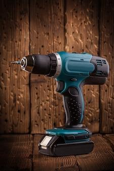 Chave de fenda elétrica azul sobre fundo de madeira rústica