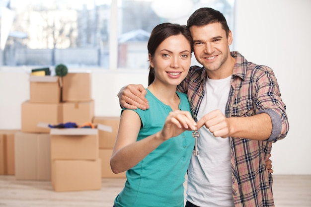 Chave de sua nova casa. jovem casal feliz parado perto um do outro sorrindo enquanto segura a chave da casa