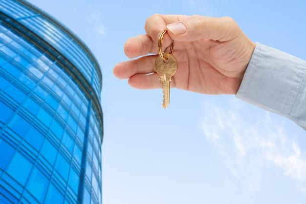 Chave do apartamento na mão de um homem contra um edifício moderno. venda e aluguel de imóveis.