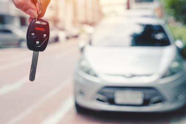 Chave do carro closeup com botão de controle remoto de segurança com desfoque de fundo do veículo para alugar, dirigir um carro ou comprar um novo conceito de carro.