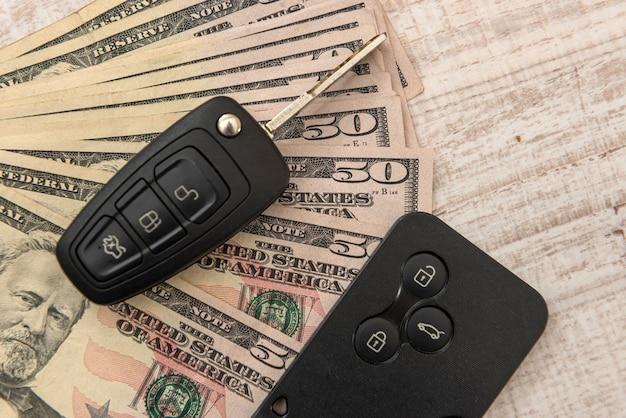 Chave do carro com controle remoto e dinheiro. oferta