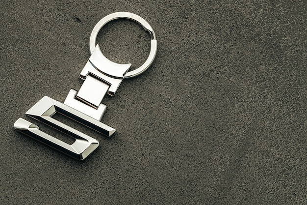 Chave do carro de metal número 5 em fundo escuro de concreto close-up