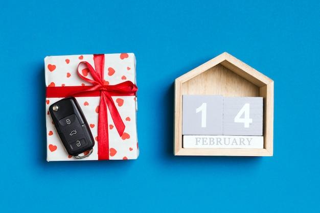 Chave do carro em uma caixa de presente com corações vermelhos e calendário festivo