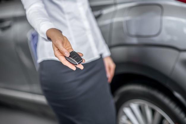 Chave do carro. mão fina e graciosa de mulher de blusa branca segurando a chave do novo carro cinza, rosto invisível