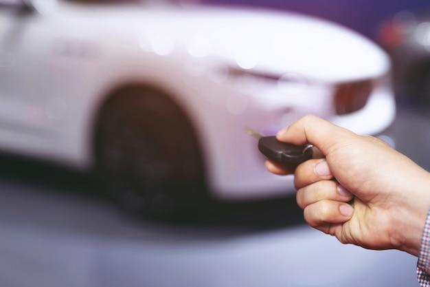Chave do carro na mão do homem de negócios. prensas manuais nos sistemas de alarme do controle remoto.