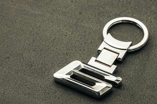 Chave do carro número seis de metal em fundo escuro de concreto close-up