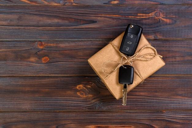 Chave do carro preto em uma caixa de presente na mesa de madeira