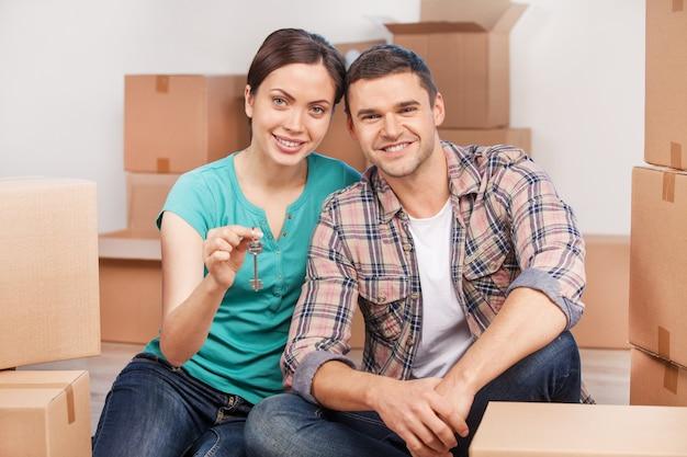 Chave do novo apartamento. jovem casal alegre sentado perto um do outro sorrindo enquanto segura a chave da casa
