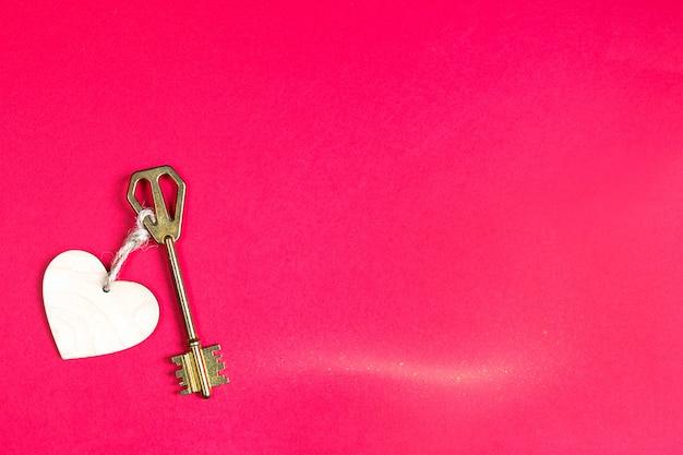 Chave dourada com etiqueta de madeira em forma de coração sobre fundo vermelho. dia dos namorados, declaração de amor, copie o espaço. sentimentos abertos e fechados. doce lar, imóveis