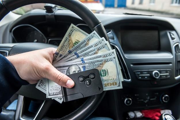 Chave e dólar do carro na mão dentro do automóvel. conceito de finanças