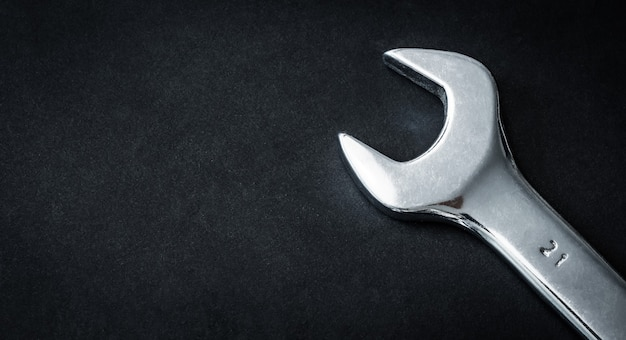 Chave inglesa de mão metálica em fundo escuro