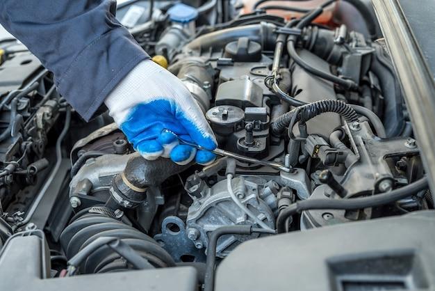 Chave inglesa e ferramenta de reparo de carro na mão do mecânico para manutenção na garagem