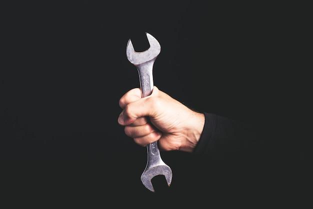 Chave inglesa - ferramentas em uma mão de homem - conceito de sercice de manutenção