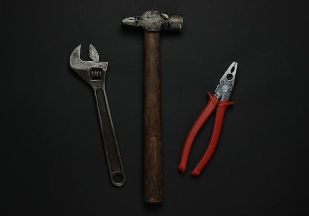 Chave inglesa, martelo, alicate em um fundo preto. ferramentas e instrumentos para trabalhadores. vista do topo