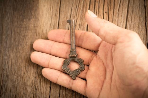 Chave na mão com fundo de madeira velho, foco seletivo.