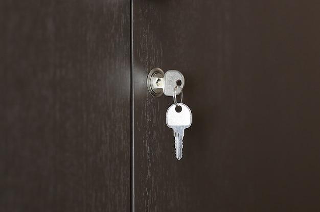 Chave no buraco da fechadura no armário de madeira, chave no bloqueio.