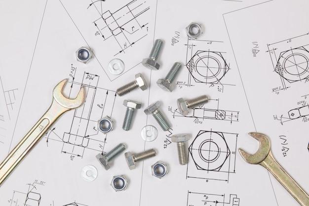 Chave, parafusos e porcas sobre desenhos de engenharia.
