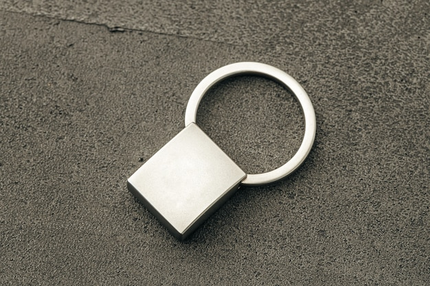 Chave pendente de metal em fundo escuro de concreto close-up