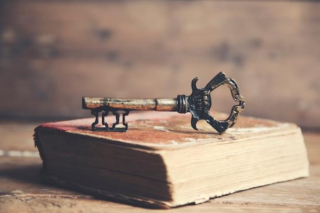Chave retrô e livro na mesa de madeira