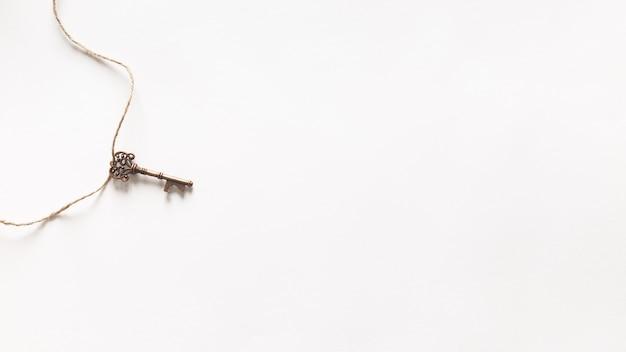 Chave vintage pendurado no fundo branco