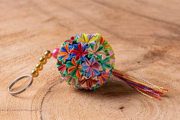 Chaveiro colorido de origami feito à mão em um fundo de madeira