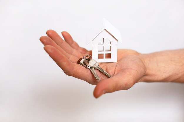 Chaveiro com as chaves da casa na mão de um homem em um fundo branco. agente imobiliário, venda de casa nova, hipoteca, mudança, banca, reparação e construção