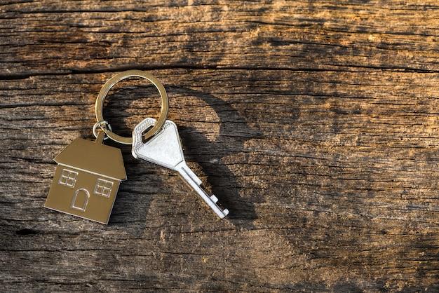 Chaveiro com símbolo de casa em fundo de madeira. conceito de empréstimo hipotecario.