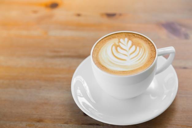 Chávena de café com uma lâmina de trigo desenhado na espuma